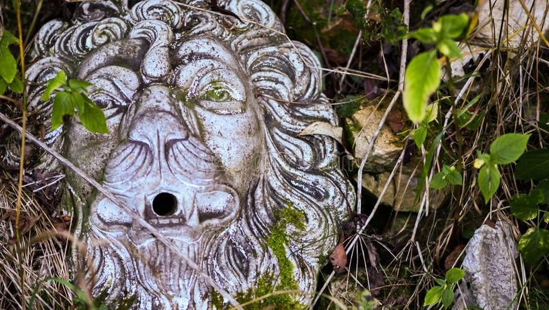 Parte do jardim coberto de vegetação Máscara da pedra do leão, escultura do jardim foto de stock royalty free