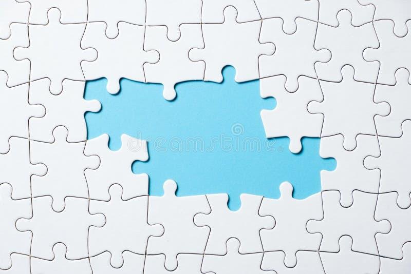 Parte do jogo do enigma de serra de vaivém no fundo azul para o projeto do tema do negócio imagem de stock
