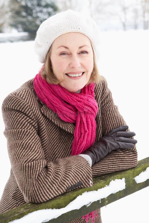 Parte esterna diritta della donna maggiore nel paesaggio dello Snowy immagini stock