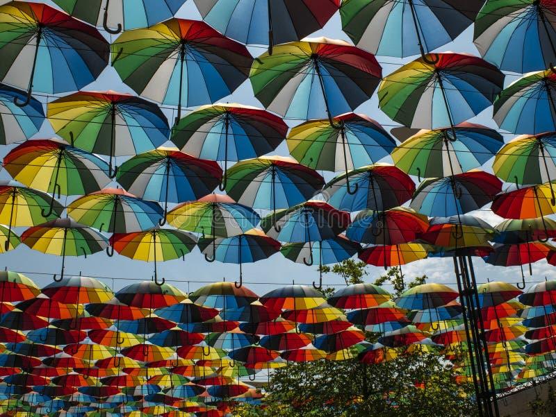 Parte externa colorida dos guarda-chuvas como a decoração guarda-chuvas de cores diferentes contra o céu e o sol fotografia de stock royalty free