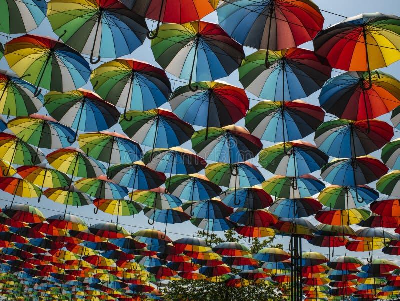 Parte externa colorida dos guarda-chuvas como a decora??o guarda-chuvas de cores diferentes contra o c?u e o sol imagem de stock