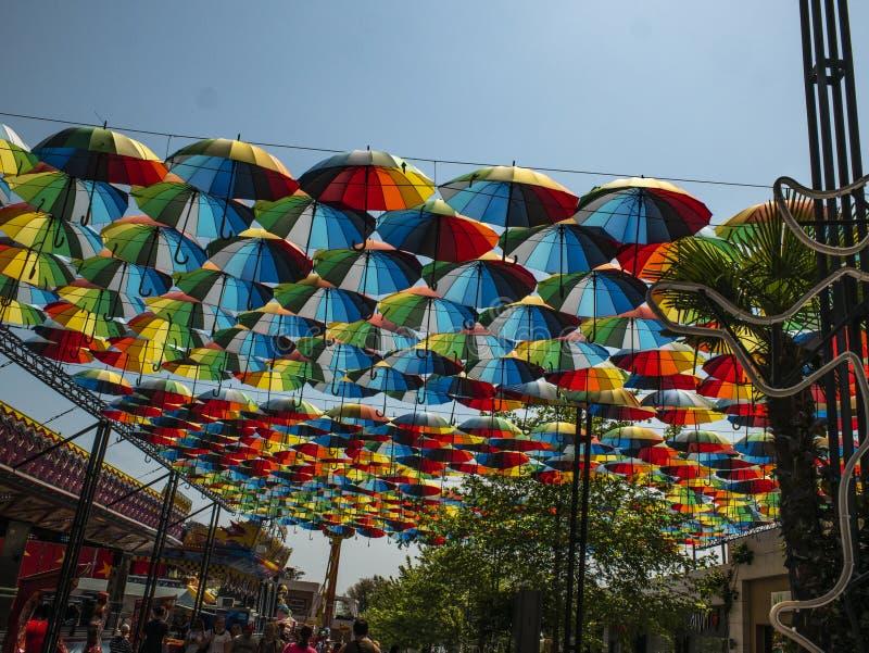 Parte externa colorida dos guarda-chuvas como a decora??o guarda-chuvas de cores diferentes contra o c?u e o sol imagens de stock