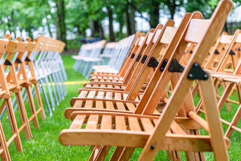Parte externa de madeira das cadeiras no parque na chuva Gotas vazias do auditório, da grama e da água imagem de stock
