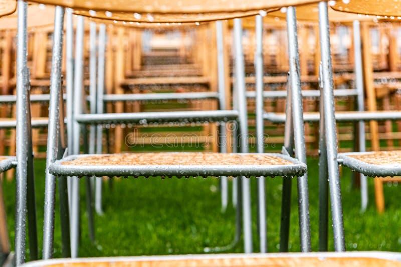 Parte externa de madeira das cadeiras no parque na chuva Gotas vazias do auditório, da grama e da água fotografia de stock royalty free