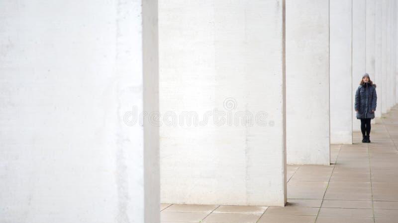 Parte externa ereta da jovem mulher na extremidade da parede imagens de stock