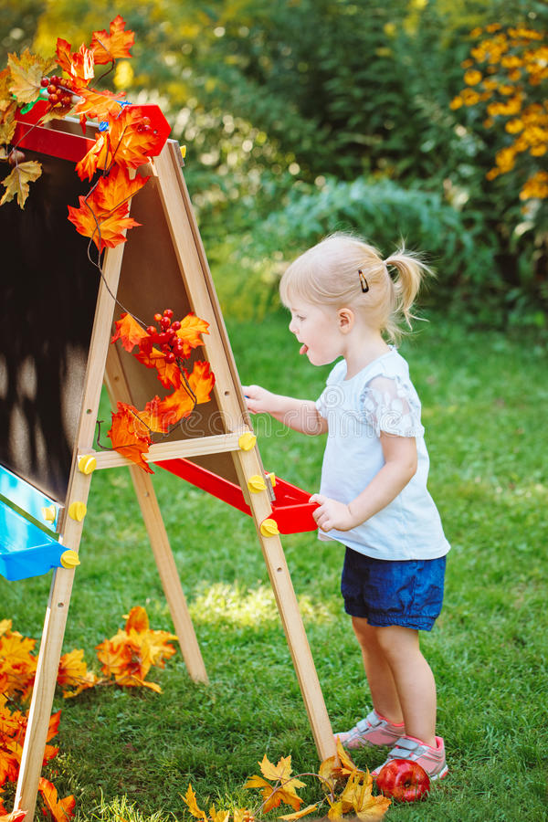 Parte externa ereta da menina caucasiano branca da criança da criança da criança no desenho do parque do outono do verão na armaç imagens de stock royalty free
