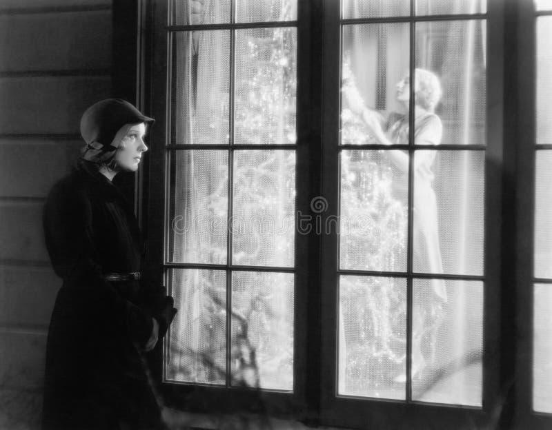 Parte externa ereta da mulher de uma janela que olha uma mulher aparar uma árvore de Natal (todas as pessoas descritas não são um imagens de stock