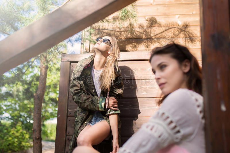 Parte externa ereta da mulher na moda nova no sol com seu amigo imagem de stock royalty free