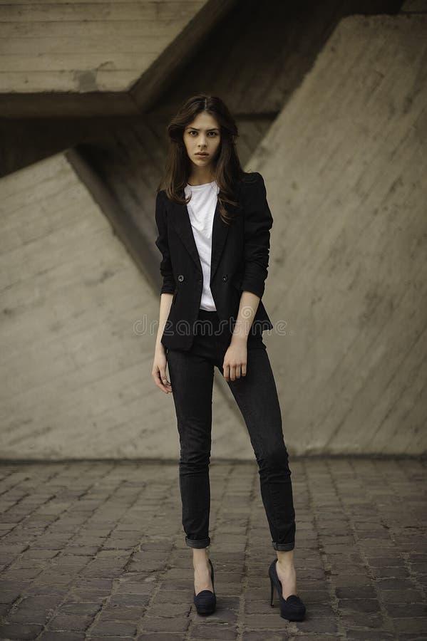 Parte externa ereta da mulher triguenha nova no revestimento preto, calças de brim que vestem montes horizontal imagem de stock royalty free