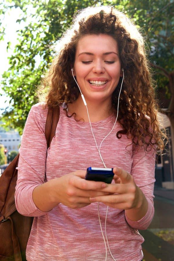 Parte externa ereta de sorriso da menina adolescente com móbil e fones de ouvido foto de stock