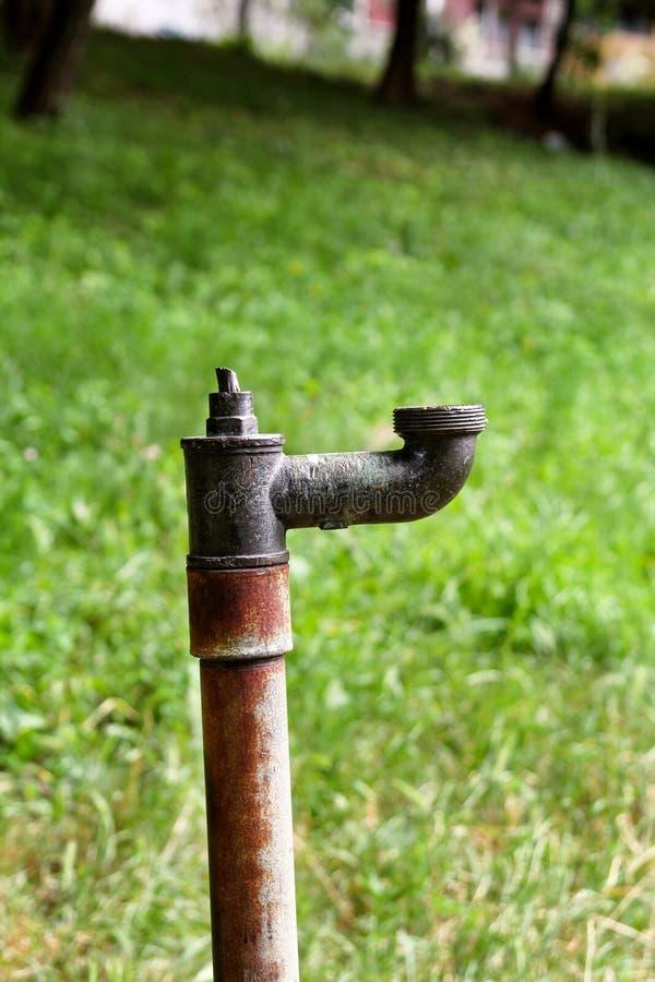Parte externa/torneira velhos das tubulações de água com a torneira de água oxidada velha do fundo da natureza/A no jardim foto de stock