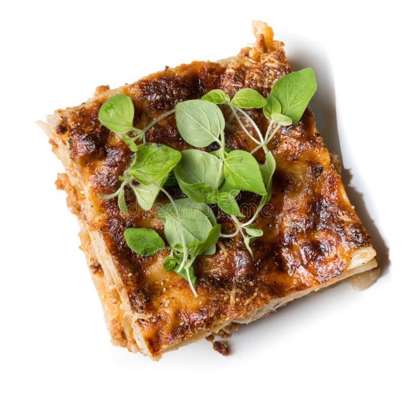 Parte fresca di lasagne con origano isolato su bianco immagini stock libere da diritti