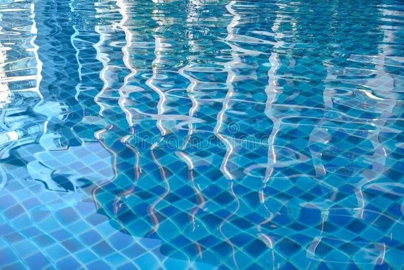 Parte inferior da piscina com fundo textured da superfície clara da água imagem de stock