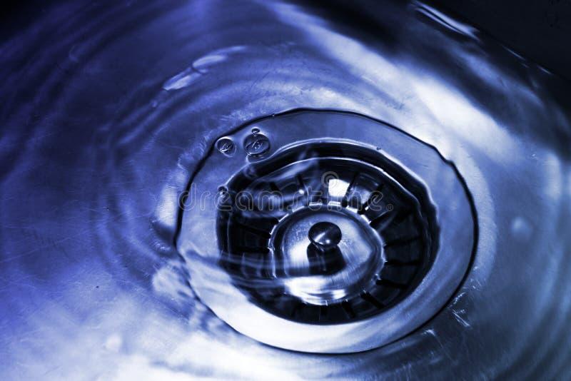 A parte inferior de uma banca da cozinha com um dreno emergente é enchida com água azul clara foto de stock royalty free