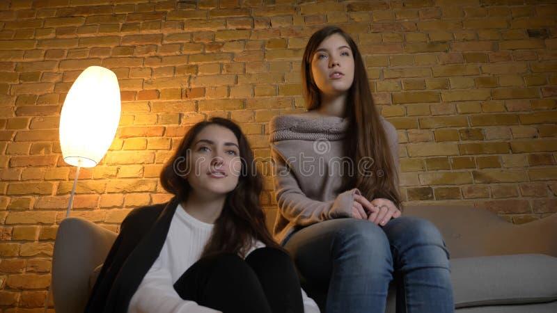 Parte inferior del primer encima del retrato de dos mujeres bonitas jovenes que miran una película TV en un apartamento acogedor  fotos de archivo