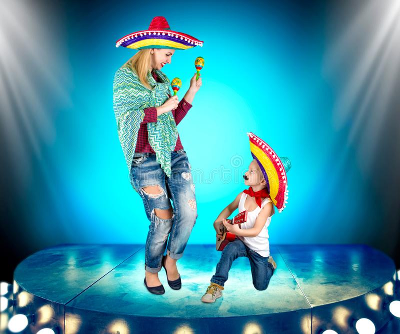 Parte mexicana Un pequeño muchacho en un sombrero toca la guitarra y canta una serenata para su madre imagenes de archivo