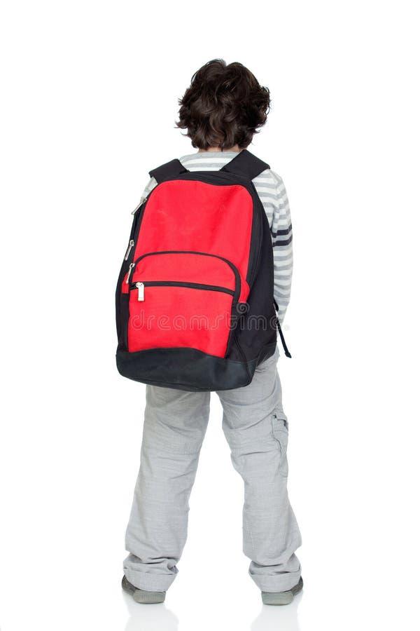 Parte posterior anónima del niño con un paquete pesado foto de archivo