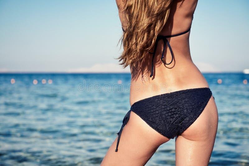 Parte posterior atractiva de una mujer hermosa en bikini negro foto de archivo