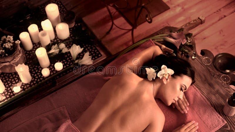 Parte posterior con las tetas al aire de la mujer del masaje en salón del balneario imagenes de archivo