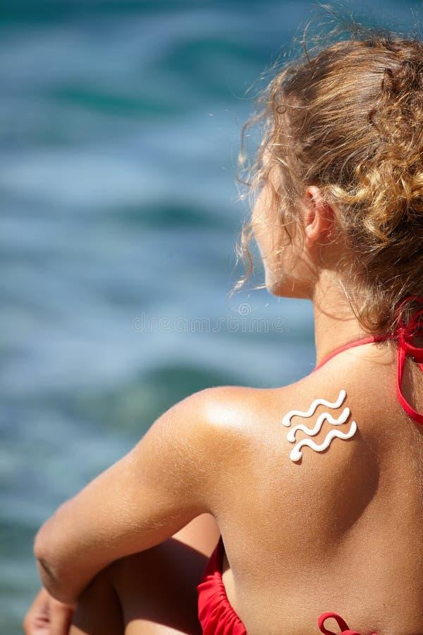Parte posterior de la mujer con quemadura y la onda de la loción del sol fotos de archivo