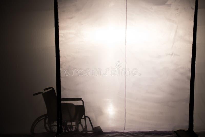 Parte posterior de la silla de ruedas de la silueta proyector blanco y de la falta de definición de la escena en el teatro imágenes de archivo libres de regalías