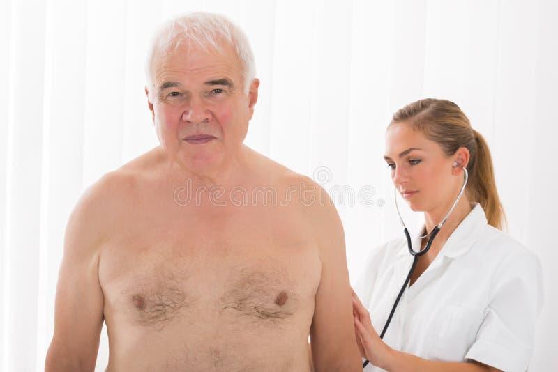 Parte posterior del ` s del doctor Examining Patient con el estetoscopio fotos de archivo