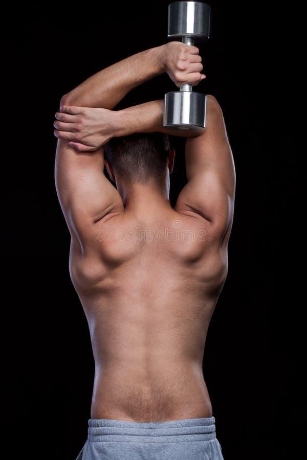 Parte posterior del varón que hace exersices aptos con pesa de gimnasia imágenes de archivo libres de regalías