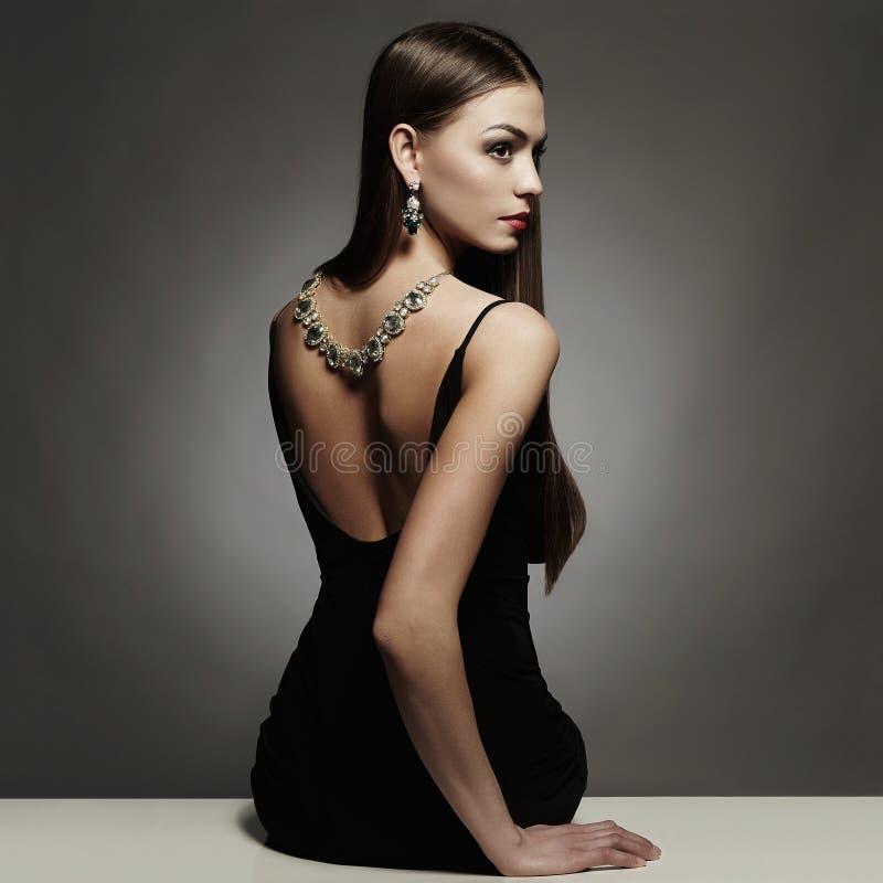 Parte posterior hermosa de la mujer joven en un vestido sexy negro muchacha de la belleza con un collar en ella detrás fotos de archivo libres de regalías