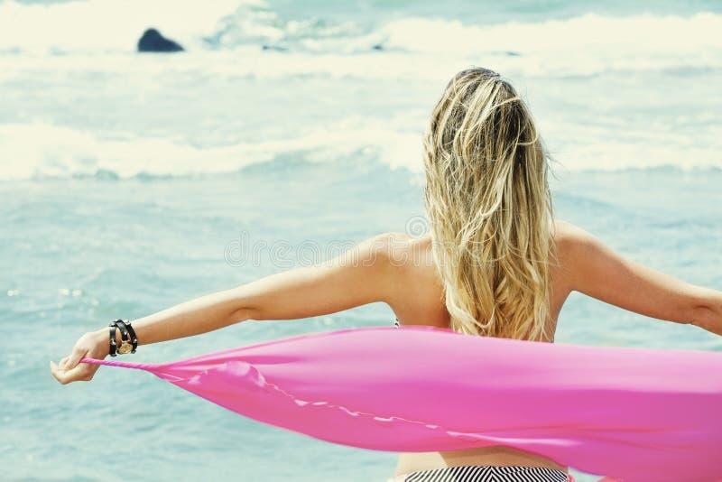Parte posterior rubia de la mujer joven con los brazos abiertos, tomando un paño de seda que mira el mar foto de archivo