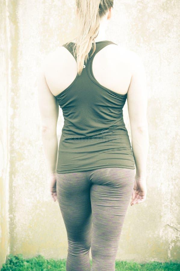 Parte posteriore atletica del ` s della donna prima di verticale immagini stock
