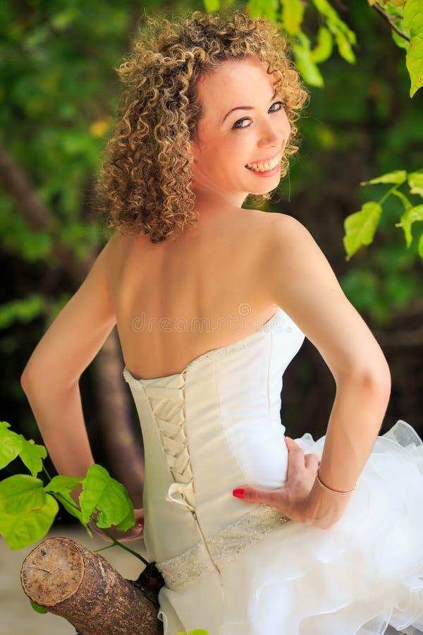 Parte posteriore del primo piano della ragazza piacevole esile in corsetto bianco di nozze fotografia stock