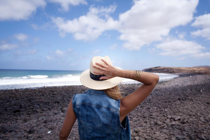 Parte posteriore della donna con il cappello Osservando sopra il mare stando su una spiaggia delle pietre fotografie stock