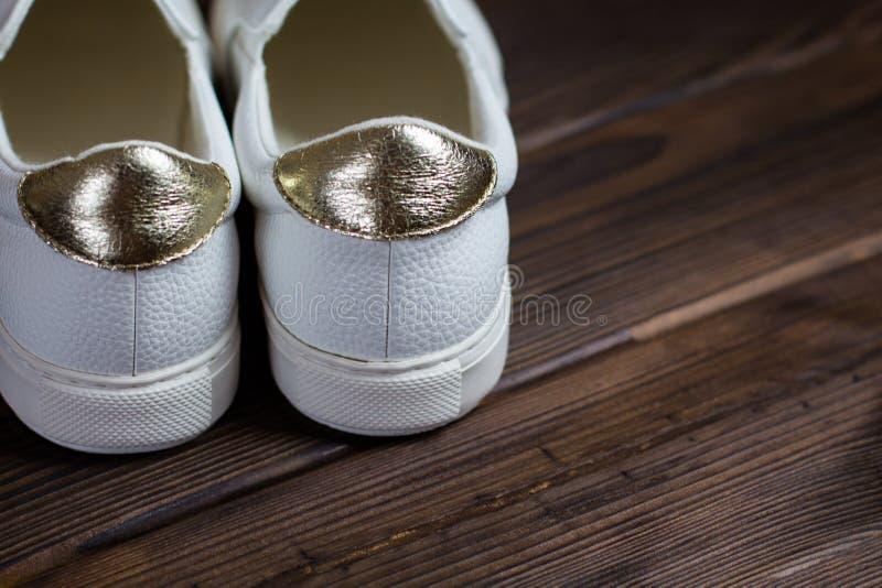 parte posteriore delle scarpe da tennis bianche sul fondo di legno di marrone scuro vista della parte di sinistra, posto per test fotografie stock