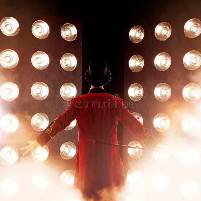 Parte posteriore dello showman, armi ai lati Giovane anfitrione, relatore o attore maschio in scena Il camisole del tipo in rosso fotografia stock