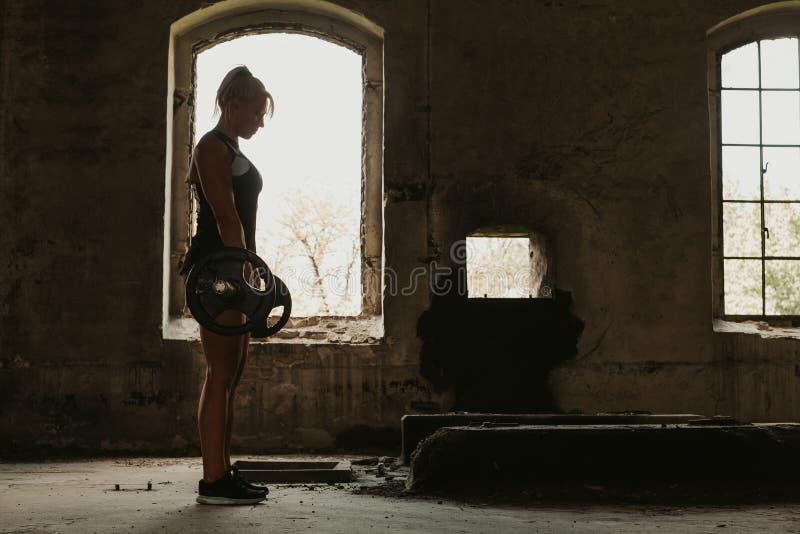 Parte posteriore di allenamento dell'atleta femminile facendo deadlift immagine stock libera da diritti