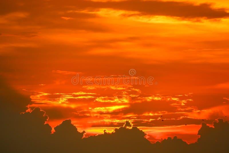 parte posteriore di tramonto sull'ultima nuvola arancio rosso-chiaro della siluetta del cielo fotografie stock libere da diritti