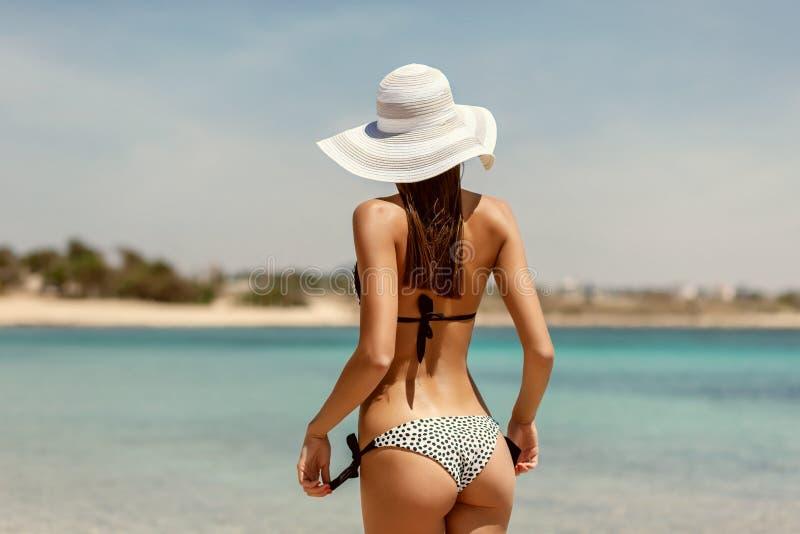 Parte posteriore sexy di bella donna in bikini sul fondo del mare Natiche sexy La retro annata ha tonificato l'immagine, simulazi fotografia stock