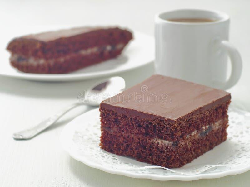 Parte quadrada de bolo de chocolate com enchimento de creme Brownies caseiros do chocolate arranjadas na placa branca Foco seleti fotos de stock
