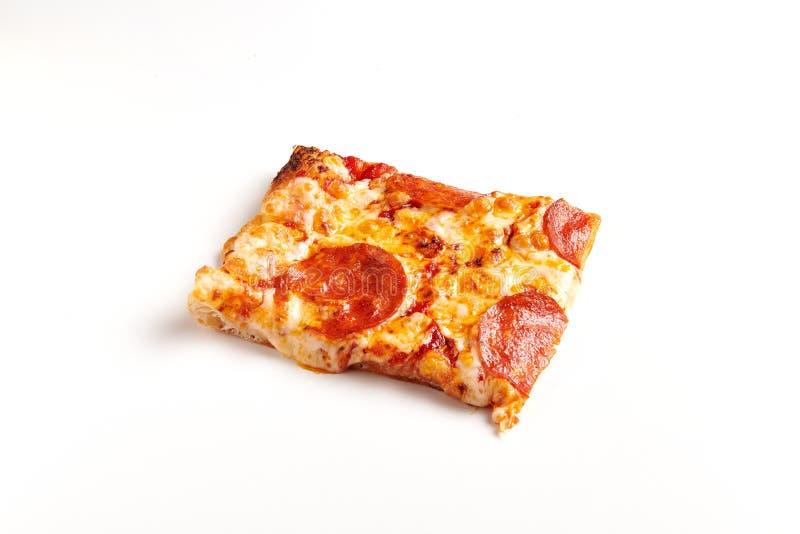 Parte quadrada de pizza de Pepperoni na tabela branca foto de stock