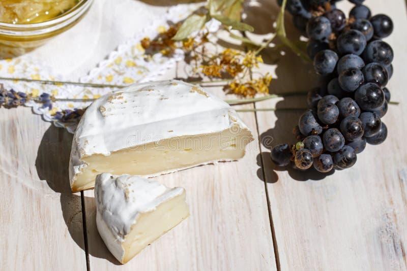 Parte redonda de queijo do brie, de uvas pretas e de alfazema em um fundo branco de madeira, vista superior Queijo do camembert F fotografia de stock