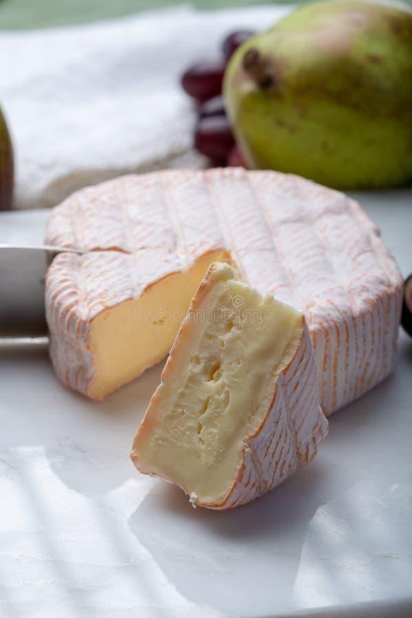 Parte redonda de queijo francês Fleur Rouge feita do leite de vaca servido como a sobremesa com figos e as peras frescos fotos de stock royalty free