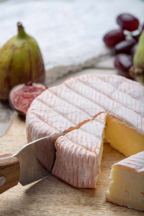 Parte redonda de queijo francês Fleur Rouge feita do leite de vaca servido como a sobremesa com figos e as peras frescos imagens de stock
