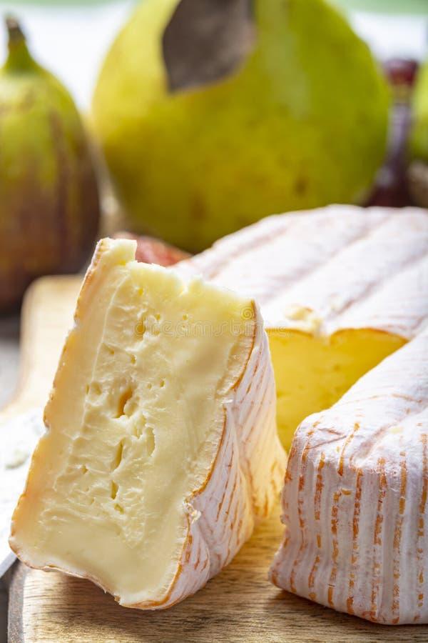 Parte redonda de queijo franc?s Fleur Rouge feita do leite de vaca servido como a sobremesa com figos e as peras frescos imagem de stock royalty free