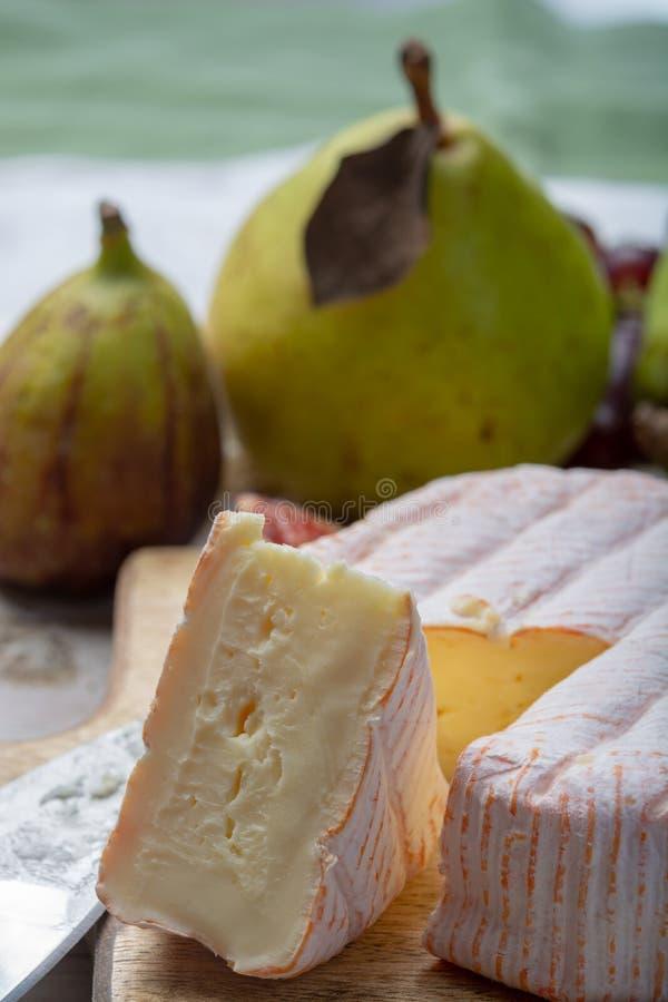 Parte redonda de queijo franc?s Fleur Rouge feita do leite de vaca servido como a sobremesa com figos e as peras frescos fotos de stock royalty free