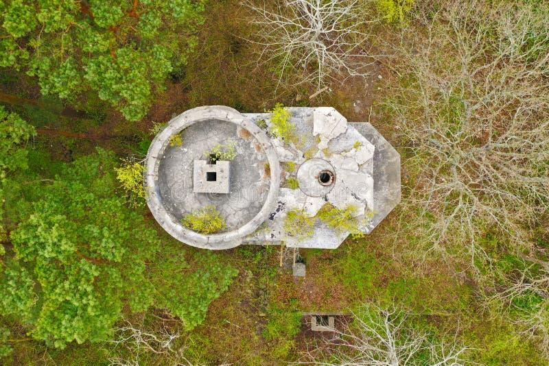 Parte superior aérea abaixo da vista no depósito arruinado e velho da torre escondido na floresta profunda imagens de stock