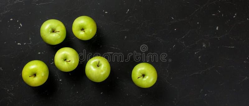 Parte superior abaixo da vista, maçãs verdes na placa de mármore escura Alimento saudável com bandeira do fruto, espaço para o te fotografia de stock