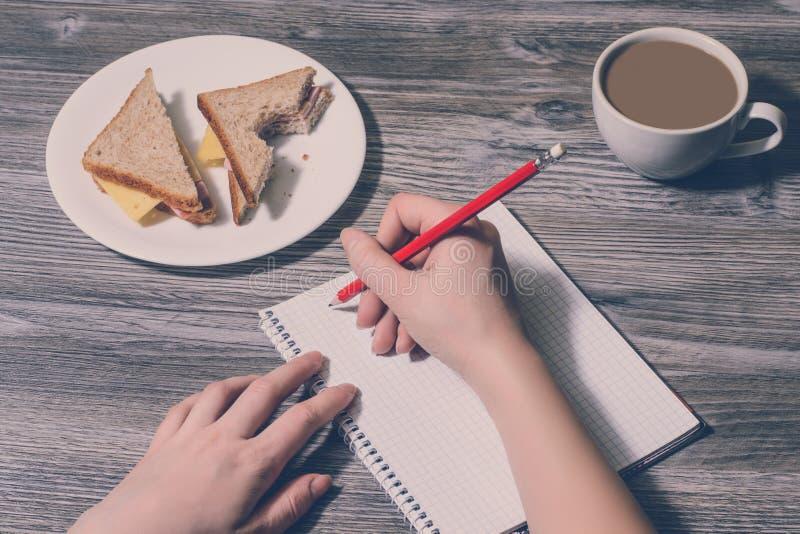 Parte superior acima do fim das despesas gerais acima da mão da escrita em um caderno e em um sanduíche saboroso em uma placa red imagem de stock royalty free