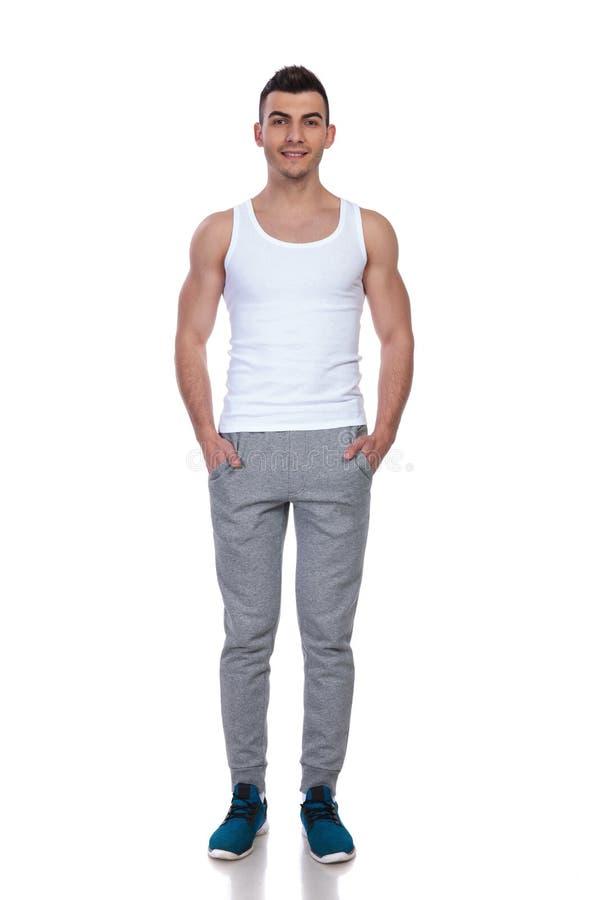 Parte superior branca vestindo do homem considerável que está com mãos em uns bolsos foto de stock