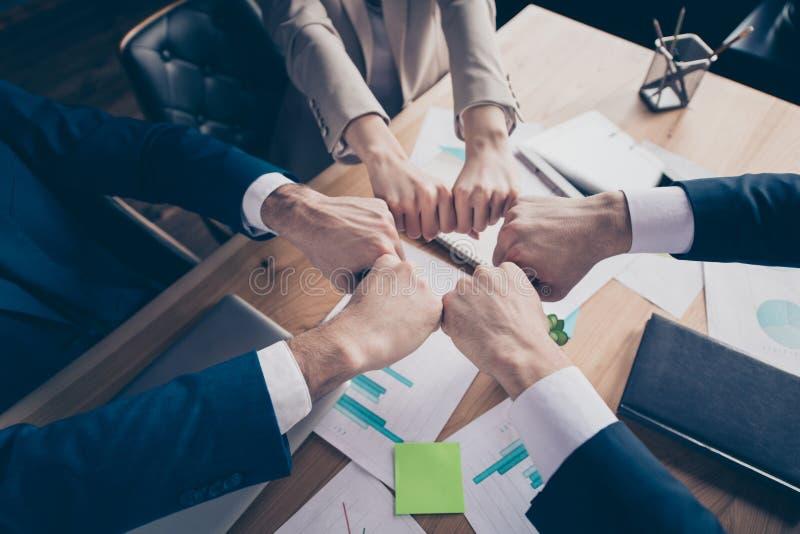Parte superior colhida acima de uma opinião de ângulo alto três gerentes de vendas à moda elegantes que unem os punhos no círculo imagens de stock