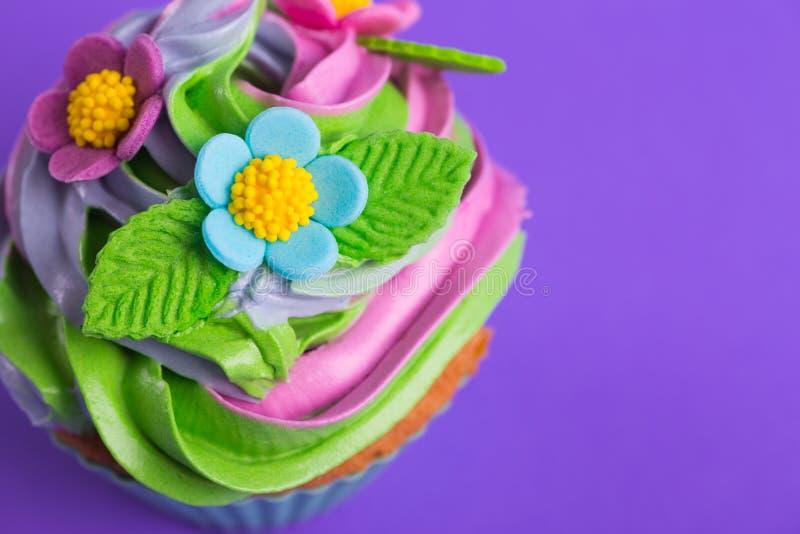 Parte superior colorido cremosa do queque do close up decorada com flores e as folhas coloridas no fundo roxo fotos de stock